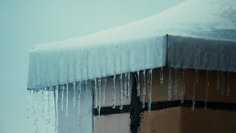 Multiple icicles and snowy sloped roofs of residential houses in winter 4K Footage