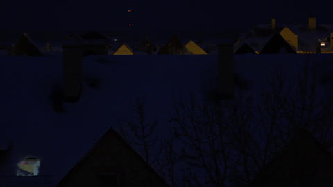 Snowy sloped roofs of residential houses at night Footage