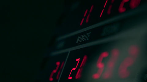 Digital clock in dark room with red glowing digits Live Action