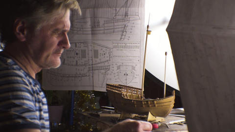 Serious man collects a model of the ship. Video Live Action