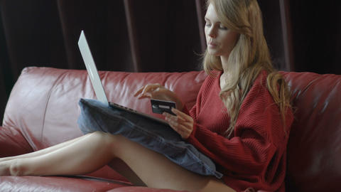 Beautiful smiling blonde woman sitting on couch using wi fi internet on her Footage