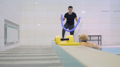 Trainer show senior woman the exercises with noodle in swimming pool Footage