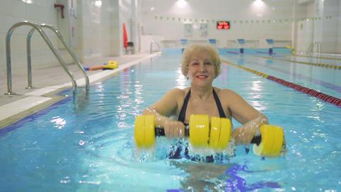 Pretty elderly woman makes exercise with dumbbells in swimming pool Footage