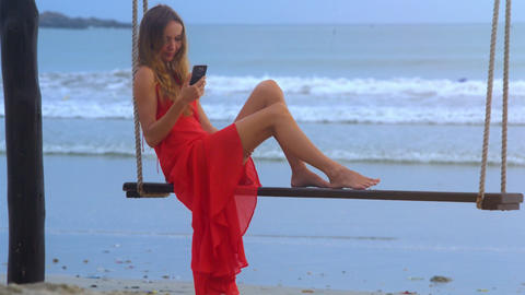 Girl Sits on Swing Chats on Phone against Wavesurf Footage