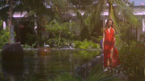Smiling Woman Walks near Fountain in Tropical Garden Footage