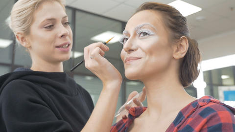 A professional make-up artist does the make-up of the model Footage