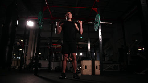 Zoom camera. the man performs lifting the bar in the gym. the camera moves Live Action