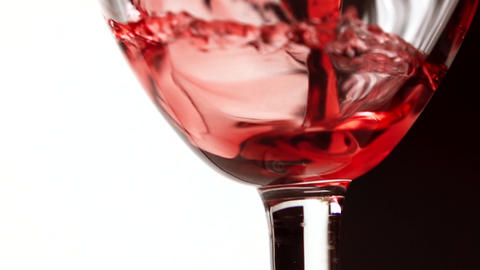 Pouring red wine into wineglass against black and white background extreme close Footage