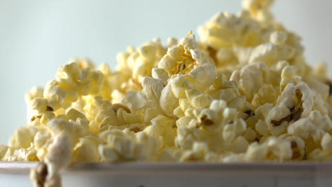 Pouring popcorn into paper box. Cinema or fast food concepts. Super slow motion Footage