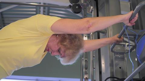 Elderly woman stretching near simulator in the gym Footage