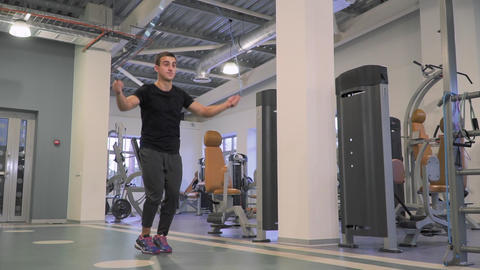 Attractive caucasian man jumps on skipping rope in the gym Footage