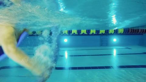 Elderly woman training to swim in the pool - shooting underwater Footage