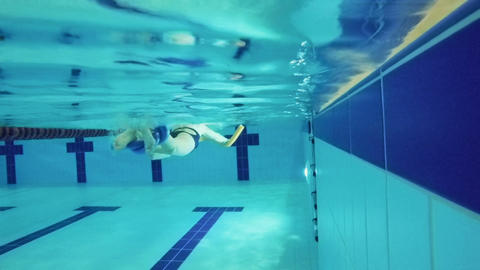 Senior woman swims with special equipment in swimming pool - underwater Footage