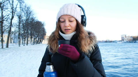 Beautiful young girl listens to music and drinks tea from a thermos in the open Footage