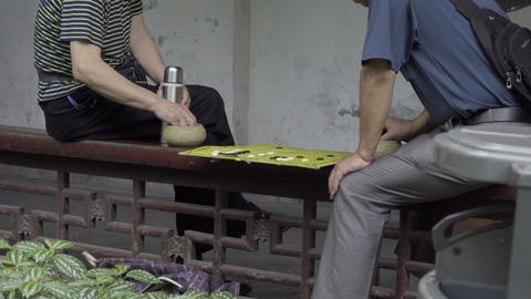 Two Chinese men playing a Chinese board game Live Action
