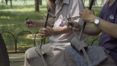Two men playing Chinese two stringed fiddles Live Action