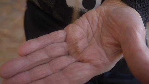 the old woman puts the Christian cross on the palm Footage
