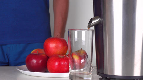 Man in blue clothes making red apple juice with shiny juicer. 4K close up shot Footage