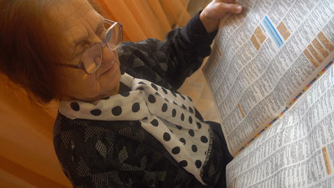 old woman in glasses reads the newspaper carefully Footage