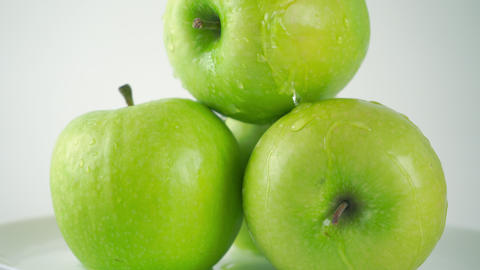 Close up 4K ProRes dolly shot of green apples and pouring water. White Footage