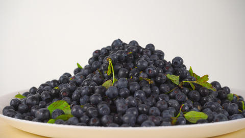 Pouring wet blueberries on a rotating plate 4K close up video Footage
