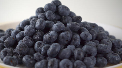 Heap of wet blueberries on a rotating plate 4K close up ProRes video Footage