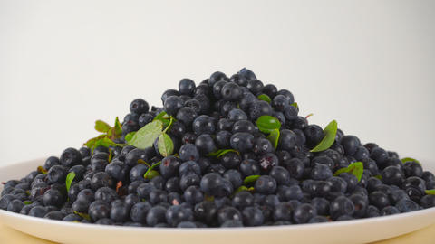 Pile of wet whortleberries with leaves on a rotating plate 4K close up ProRes Footage