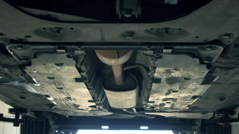 Bottom of the car and exhaust pipe 4K zoom in shot. Car maintenance at service Live Action