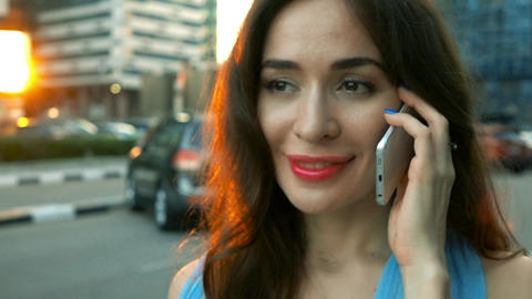Portrait of happy brunette girl talking on her smartphone on the street. Super Footage