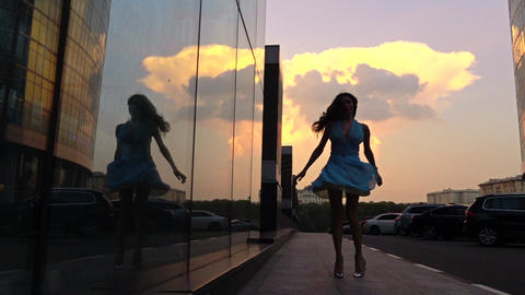 Slender girl in dress spinning on the street at sunset, super slow motion shot Footage