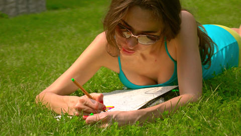 Beautiful brunette girl in sunglasses laying on the grass and drawing. 4K Footage