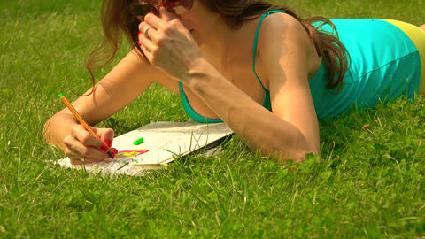 Beautiful brunette girl in sunglasses laying on the grass and colorizing. 4K Footage