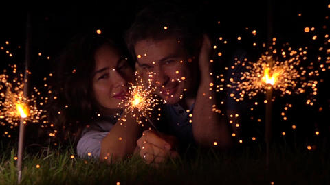 Cheerful loving girl and man laying on the grass with burning sparklers at night Footage