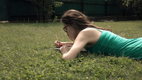 Pretty brunette laying on the lawn and drawing. 4K steadicam wide shot, bleached Footage