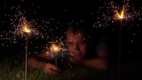 Sad lonely man with burning sparklers at night. Super slow motion video shot at Footage