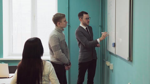 Teacher explains something on a whiteboard to students Footage