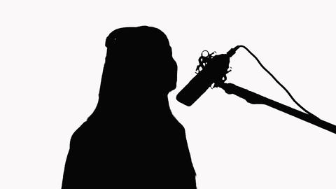 Silhouette of a young girl who sings in a studio microphone. Close-up On a white Footage
