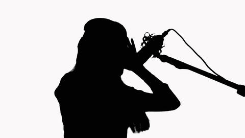 Silhouette of a young girl who sings in a studio microphone. On a white Footage