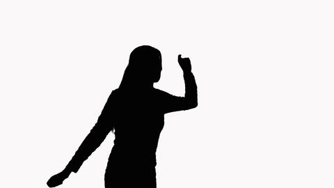 Silhouette of a girl who is dancing happily in the studio. On a white background Footage