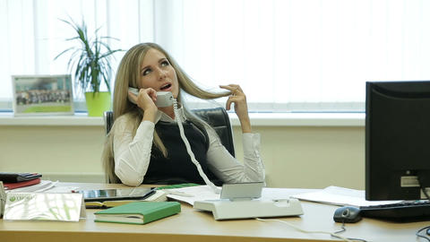 Businesswoman relaxing in the office talking on the phone Footage