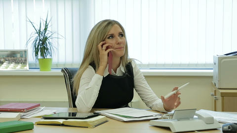 Young, pretty businesswoman with documents talking on cellphone at the office Footage