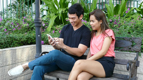 Guy and a girl sitting on a bench at Benjasiri Park watching his phone Footage