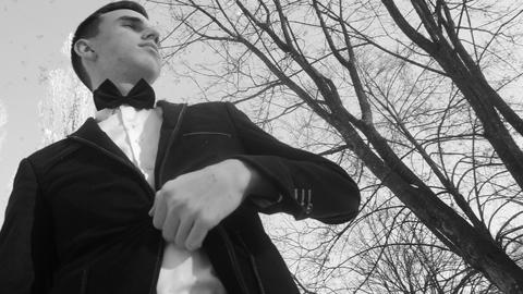 young man posing in a tuxedo in the winter against the white snow,shot in retro Footage