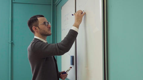 Young male lecturer writes on the whiteboard in classroom Live Action