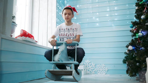 A teenager in Santa's hat sits on a children's rocking chair Footage