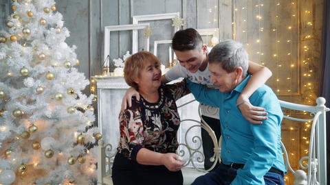 A young man hugs his grandmother and grandfather. New Year photo session Footage