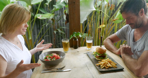 Attractive man and woman couple celebrating with beer and food in a restaurant Live Action