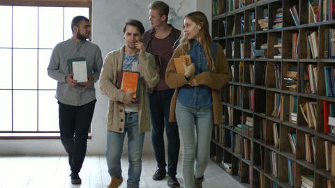 Group of students with books walking in library Footage