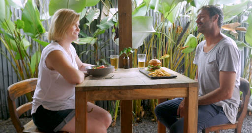Push in of an attractive couple celebrating with a cold beer and a meal in a Footage