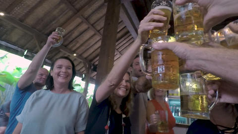 POV of a large group of people toasting and cheering a man holding a beer glass 画像